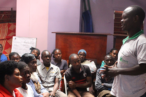 Benard Ogoi, AMWIKs Programs Officer speaking to members of the Kibera Radio Listening Group. Looking on is Esther Njogu, a Social worker with NFSS